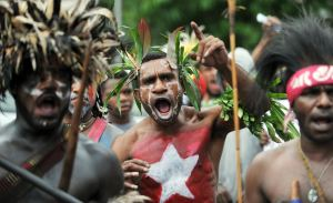Papuan protesters, with their bodies and faces painted displaying the banned Morning Star flag, shout at a rally marking the 50th anniversary of the region's claim to independence in eastern Indonesia's restive region of Papua, at a demonstration in Jakarta on December 1, 2011. On December 1, 1961, Papuans first raised the Morning Star flag and sang a new national anthem after being granted freedom from more than 130 years of Dutch colonial rule. Displaying separatist symbols such as the Morning Star is considered an act of treason in Indonesia under the criminal code and several perpetrators are serving 20-year jail terms for the offence.   AFP PHOTO / Bay ISMOYO